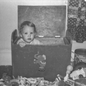Adrian in his toy box