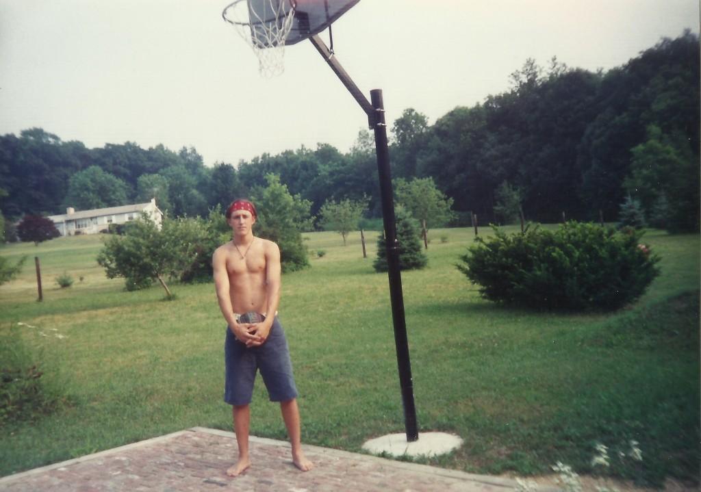 Adrian holding basketball in high school