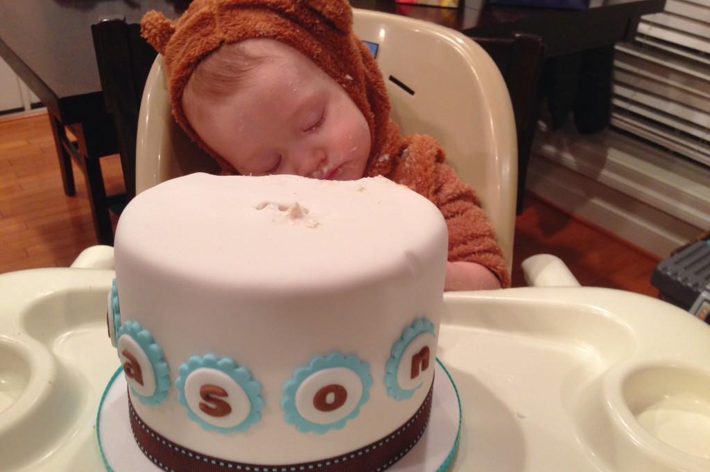 Mason asleep on his cake