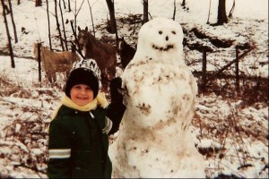 Adrian with snowman as a kid